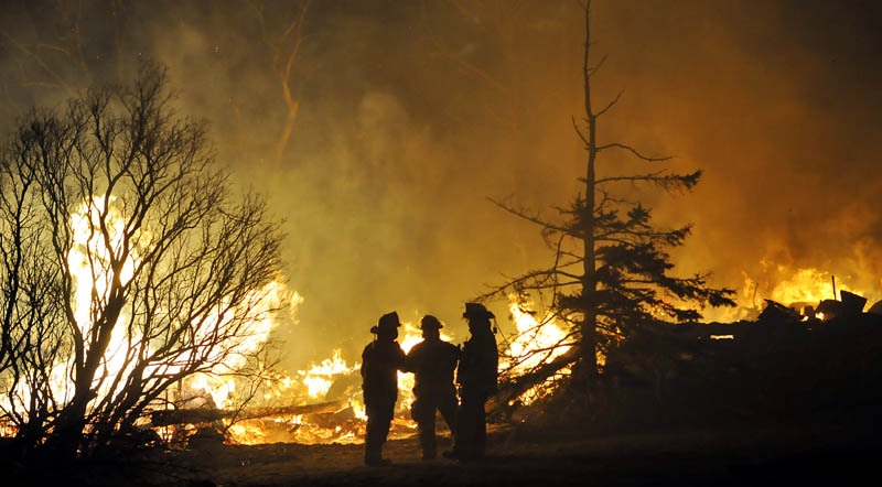 Firefighters confer next to the burning barn of a farmhouse that burned Thursday on the Crummett Mountain Road in Somerville.