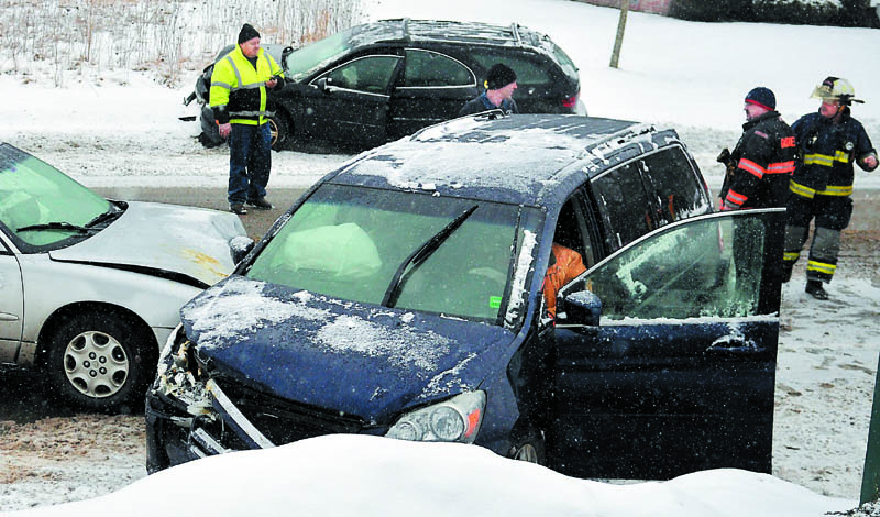 Farmingdale and Gardiner firefighters approach vehicles that collided Wednesday on Maine Avenue in Farmingdale. Accidents were reported across Maine as several inches of snow fell.
