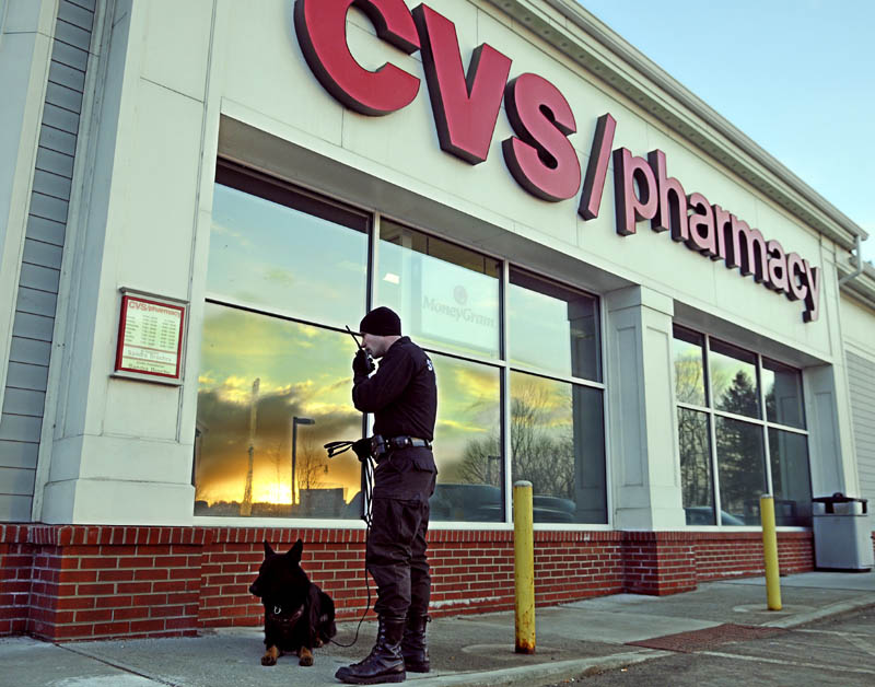 ROBBED: Cpl. G.J. Neagle of the Kennebec County Sheriff's Office speaks on the radio late Tuesday afternoon outside the CVS pharmacy on Stone Street in Augusta moments after it was reportedly robbed. Police were pursuing the robbers on foot, by vehicle and with dogs, such as Neagle's.