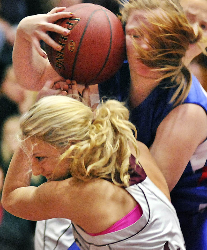 Monmouth Academy's Melissa Brassard, left, battles for a rebound with Oak Hill High School's Grace Sabine on Monday in Monmouth. The Mustangs beat the Raiders 46-40