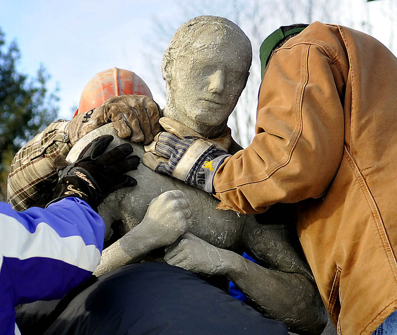 People attach a concrete human figure Sunday, while installing a sculpture at the Viles Arboretum in Augusta, which was created by University of Maine at Augusta students.