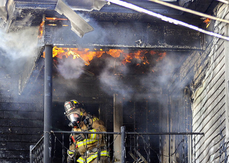 An Augusta firefighter ducks beneath flames emerging from the third-floor deck of an apartment building that burned Thursday on Sewall Street.