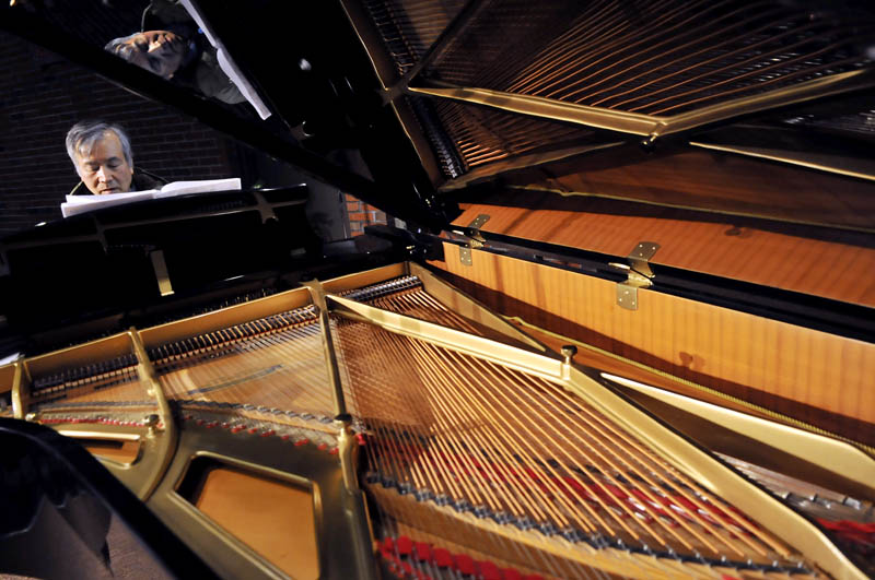 Pianist Masanobu Ikemiya rehearses Sunday on a grand piano donated to the University of Maine at Augusta by the school's Senior College. Ikemiya performed during a concert at Jewett Auditorium at UMA.