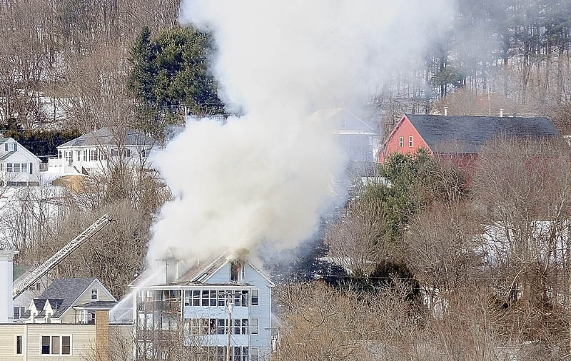 The Augusta fire department's ladder truck can be seen at left, as smoke pours from the roof of 1 Penobscot St. in a photo taken Tuesday afternoon from the east side of Augusta.