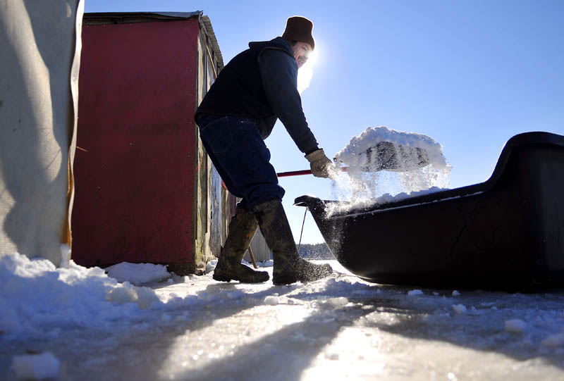 """Matt Baker shovels snow up against a smelt shack Wednesday at his family's Pittston business, Baker's Smelt Camps. Baker and his family picked snow up from the river to insulate the exterior of the camps in temperatures, with the wind chill, that were well below zero. """"I like the cold,"""" Baker said."""