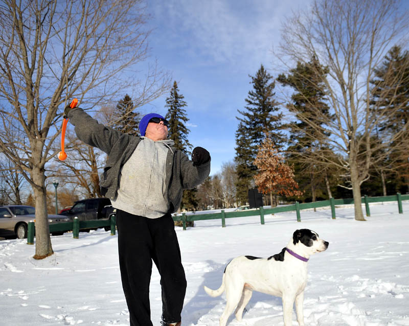 """Jerry Ashlock, of Augusta, hurls a ball for his dogs on Thursday, in Augusta. Ashlock said his pair of rescue dogs need to """"run around every day"""" to keep fit."""