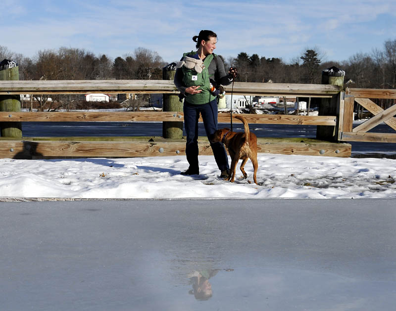 Nettie Pangallo, of Richmond, leads her dog past the ice rink at the Gardiner waterfront on the Kennebec River on Monday, while taking her infant son, Atticus, for a walk in temperatures in the mid-50s F. Temperatures are forecast to drop later this week.