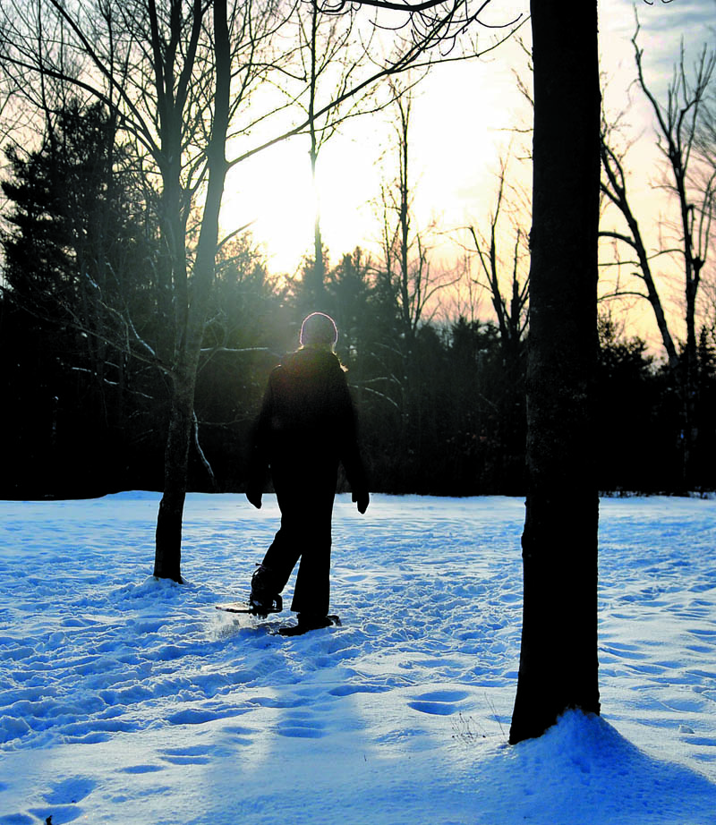 """Jessica St. Amand, of West Gardiner, walks into the woods on a pair of snowshoes Thursday in Hallowell. St. Amand was taking a break from appointments as a massage therapist """"to get a little exercise."""""""