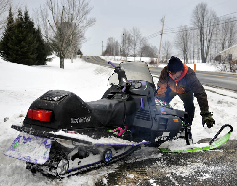 Larry Murphy moves a snowmobile off a patch of tar in a driveway Wednesday while commuting home from his job in Augusta. Murphy said he hit a soft patch of snow, forcing him to detour across the driveway.