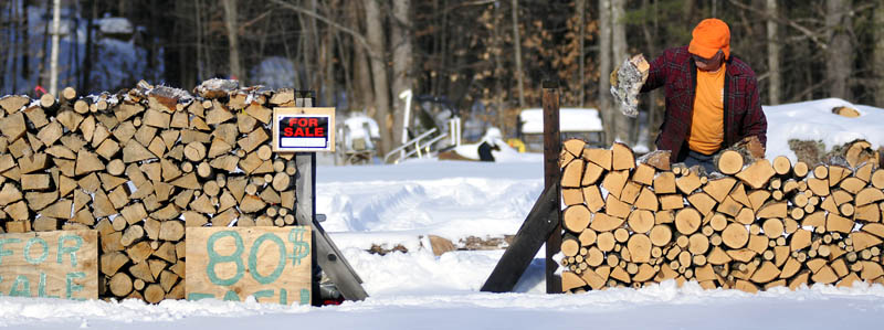 Richard Cormier piles firewood he cut at his Farmingdale lot, on Tuesday. Cormier said he's selling the freshly cut hardwood by the third of a cord.