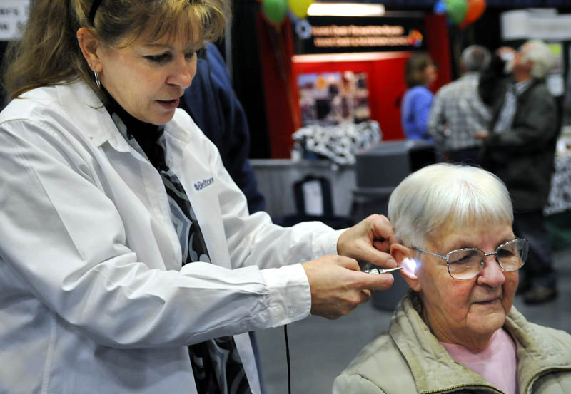 Christine Gay, of Vassalboro, gets her hearing checked Wednesday by Lisa King, of Beltone, during the Maine Agricultural Trades Show in Augusta. The free hearing checkup for guests was provided by Maine AgrAbility, which assists farmers with chronic health issues across the state.