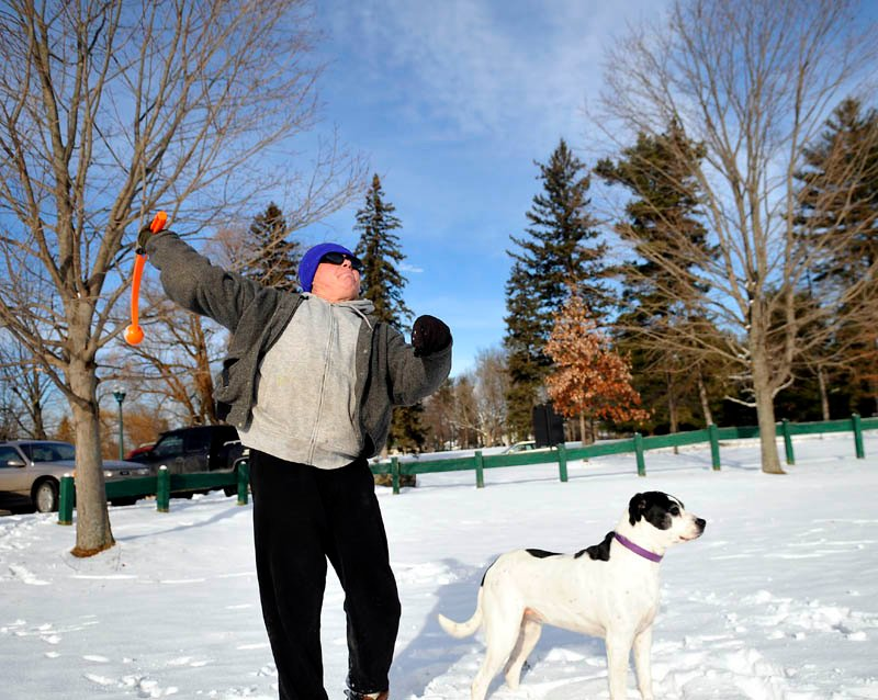 "Jerry Ashlock, of Augusta, hurls a ball for his dogs on Thursday, in Augusta. Ashlock said his pair of rescue dogs need to ""run around every day"" to keep fit."