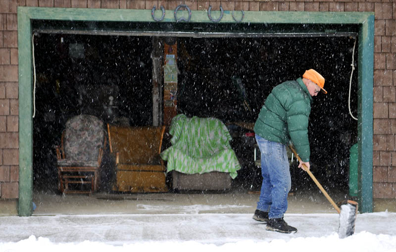 Ernie McPherson battles sleet and snow late afternoon Wednesday while clearing out around his Farmingdale home. McPherson, 85, said he was cutting paths with a broom where his plow couldn't reach, near the barn where he holds court with his son, Ned, and several nephews.