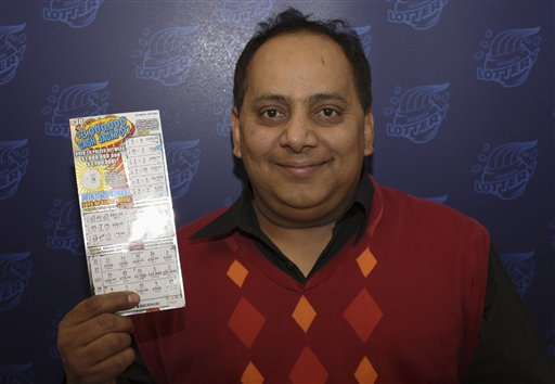 This photo provided by the Illinois Lottery shows Urooj Khan, 46, posing with a winning instant lottery ticket.