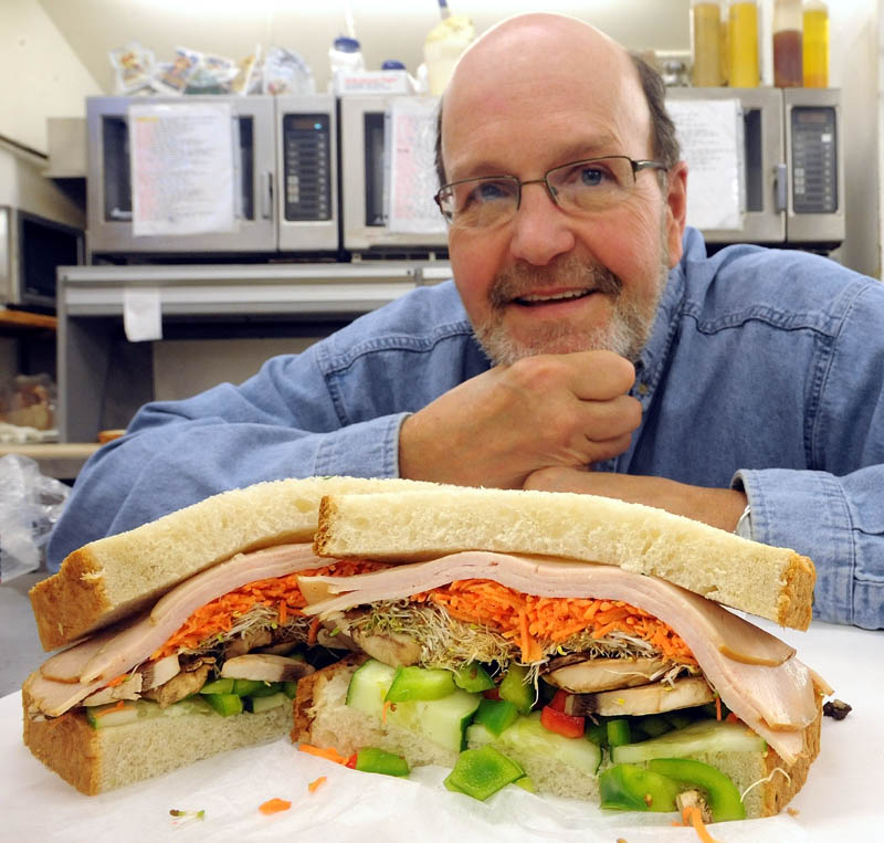 Gerry Michaud, co-owner of Big G's Deli on Benton Avenue in Winslow, poses next to his renamed sandwich, the 41,470, in recognition of the number of U.S. combat deaths in the Vietnam conflict. The sandwich was formerly named the Jane Fonda.