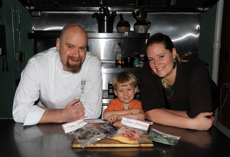Mark and Kelly LaCasse with their 3-year old son, Eben, pose for a picture with a selection of frozen, gourmet cuisine at their 4 Madison Ave. location in Skowhegan on Friday.