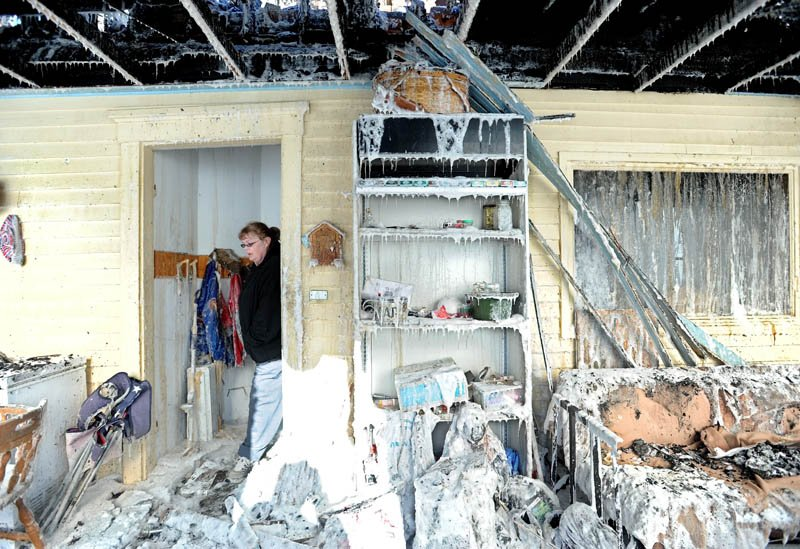 Becky Williams, 40, walks through the iced-over entryway of her parents' Madison Avenue home, in Madison, which was destroyed by fire around 3 a.m. Friday. Six area fire departments responded to the blaze in temperatures below 0 degrees.