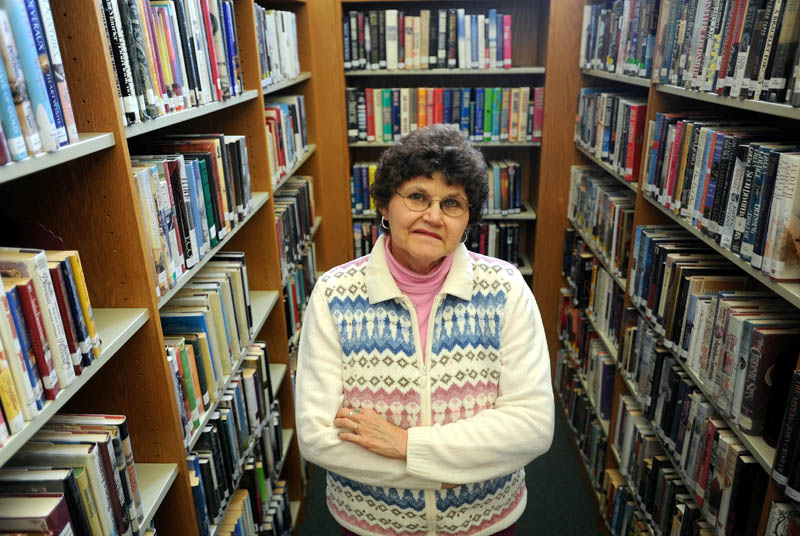 Carol Cooley, a librarian at the Oakland Public Librar,y stands among some books available for checkout on Thursday. Cooley called the police on a delinquent book borrower who failed to return $200 in books.