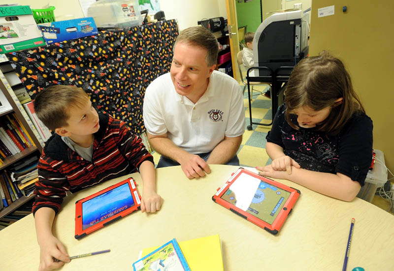 Chris Rhoda, center, a volunteer with Watch DOGS, a group of dads that volunteer at Belgrade Central School, sits with students Brandon Denardo, 8, left, and Isabell Frost, 9, in Belgrade on Friday. The group of volunteers was created to provide more of a male presence at school.