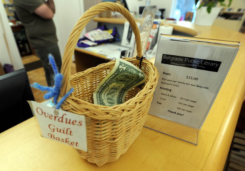 "The ""guilt basket"" is displayed on the counter at the Belgrade Public Library on Depot Road in Belgrade on Tuesday. Instead of fining patrons for overdue library books, Belgrade Public Library imposes a sort of honor system for late returns."