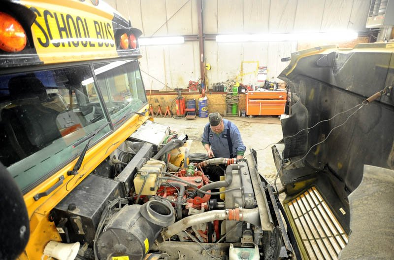 Art Jones, a mechanic at the Regional School District 18 transportation facility, repairs a power steering pump on a district school bus in Oakland on Tuesday.