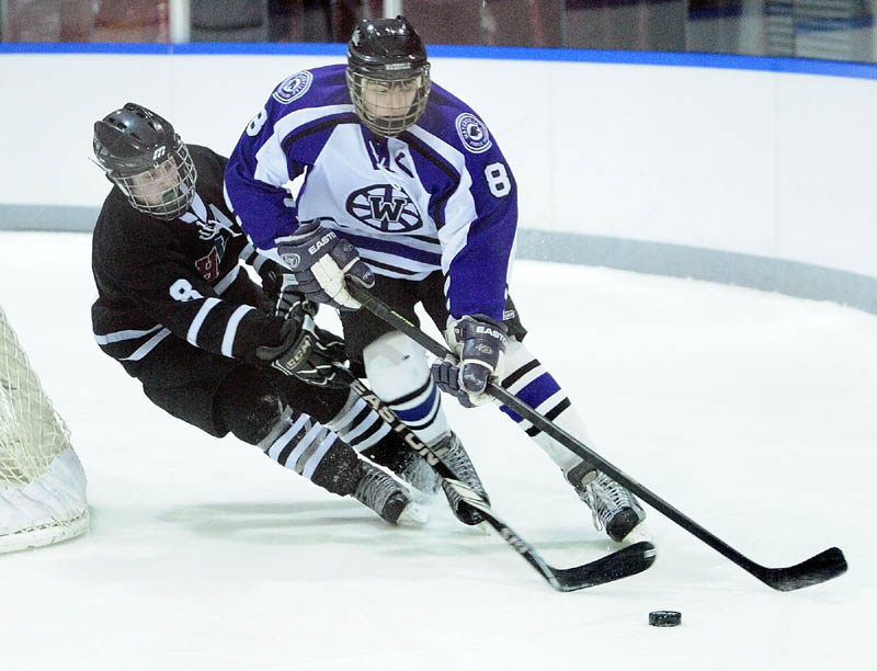 MOVE THE PUCK: MHW's Matthew Plourde, left, and Waterville senior defenseman Will Bolduc battle for a puck behind the Waterville net during MHW's 5-4 win Thursday at Colby College in Waterville.