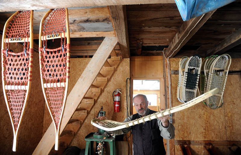 Dave Giampetruzzi, 63, of China, explains the difference of the Maine Guide snowshoe compared to the traditional designs, hanging on the left, in the workshop at Pine Grove Lodge in Bingham on Thursday.