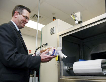 Don Stull, chief executive officer of Microzap Inc., places a loaf of bread inside a patented microwave that kills mold spores.