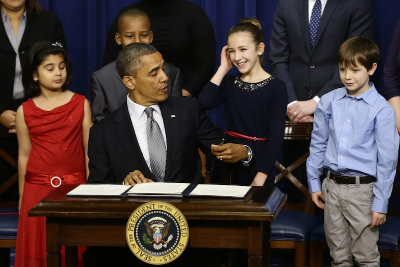 From left to right: Hinna Zeejah, 8, Taejah Goode, 10, Julia Stokes, 11, and Grant Fritz, 8, who wrote letters to President Barack Obama about the school shooting in Newtown, Conn., watch as the president jokes about being left handed as he signs executive orders outlining proposals to reduce gun violence, Wednesday, Jan. 16, 2013, in the South Court Auditorium at the White House in Washington. (AP Photo/Charles Dharapak)