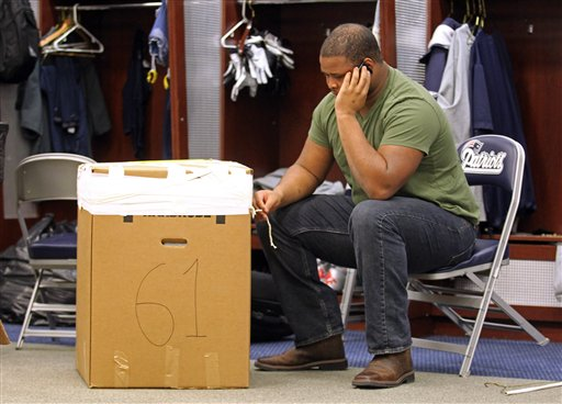 New England Patriots tackle Marcus Cannon talks on the phone next to a box of his belongings from his locker at Gillette Stadium in Foxborough, Mass., on Monday.