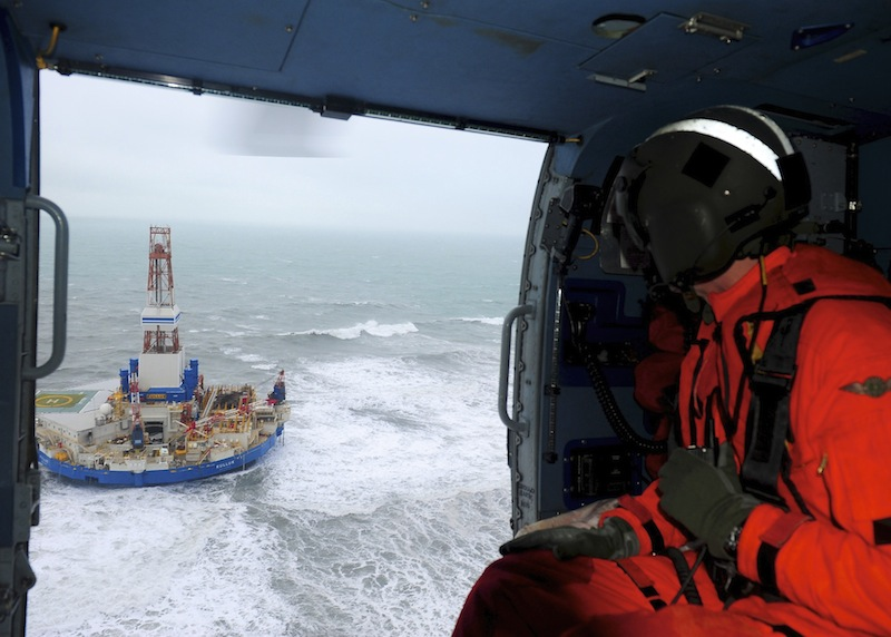 This aerial image provided by the U.S. Coast Guard shows Rear Adm. Thomas Ostebo, Incident Management Team commander, observing the Royal Dutch Shell drilling rig Kulluk aground during an overflight off a small island near Kodiak Island Tuesday Jan. 1, 2013. No leak has been seen from the drilling ship that grounded off the island during a storm, officials said Wednesday, as opponents criticized the growing race to explore the Arctic for energy resources. (AP Photo/U.S. Coast Guard, Sara Francis)