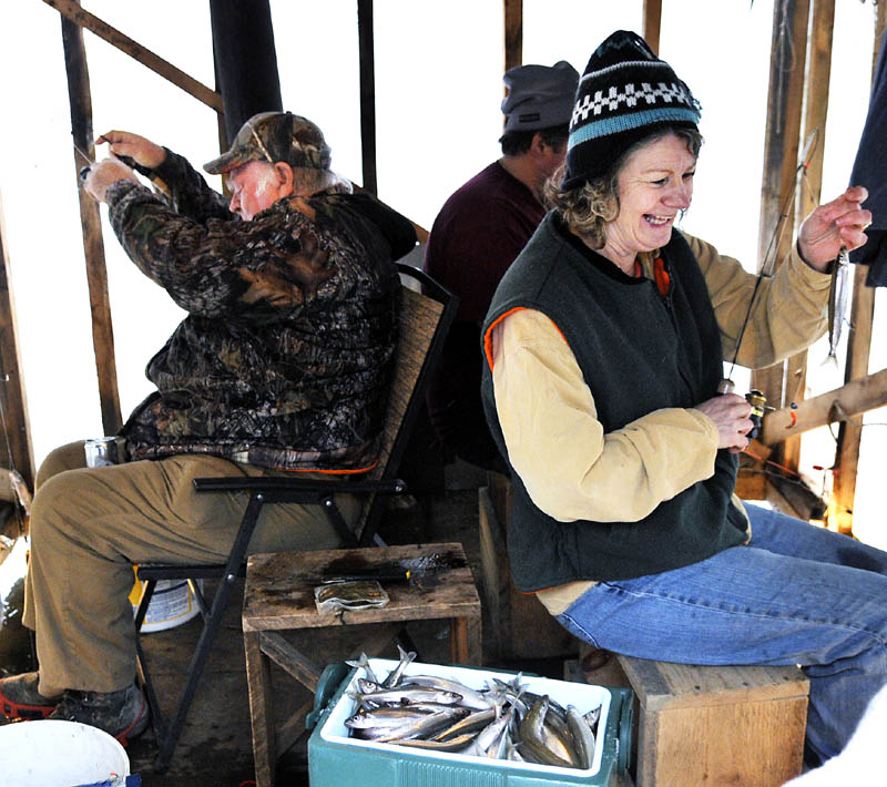 "Grace Peters, right, unhooks a smelt Sunday while fishing with Roger Cahoon, center, and Jim Earle Sr. at Baker's Smelt Camps. The winter angling shacks, rented by the tide, have emerged from Merrymeeting Bay to Randolph on the Kennebec River. The migrating fish are ""really running now,"" Baker's Smelt Camps owner Mike Baker said."