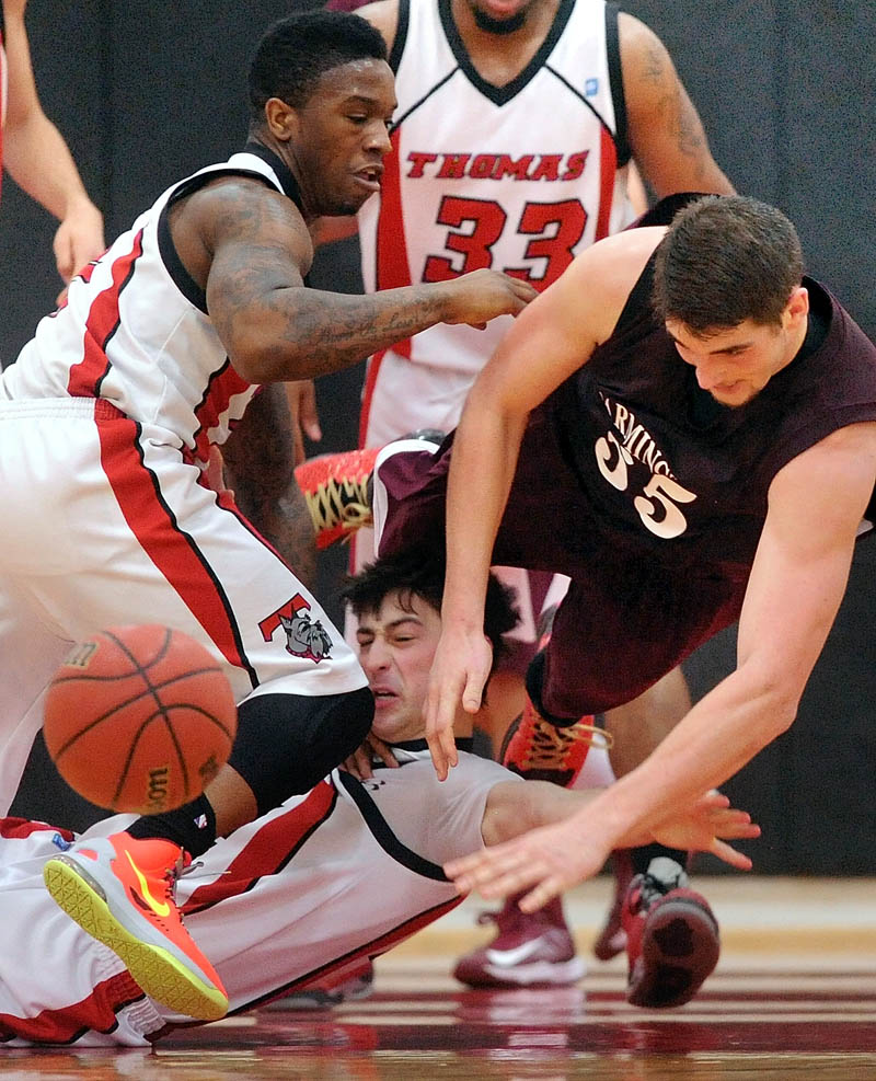 LOOK OUT: UMF's Ben Johnson,right, dives over Thomas College's Jordan Hoyt, center, in the second half in Waterville Saturday. Thomas College's Stanley Greene Jr., left, also pursues the loose ball. Farmington defeated Thomas 94-72.