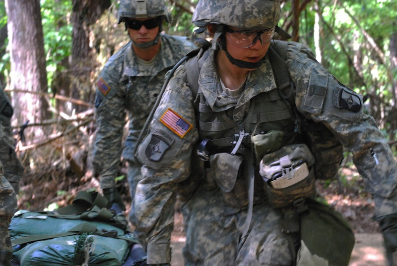 In a May 9, 2012 file photo, Capt. Sara Rodriguez, 26, of the 101st Airborne Division, carries a litter of sandbags during the Expert Field Medical Badge training at Fort Campbell, Ky. The Pentagon is lifting its ban on women serving in combat, opening hundreds of thousands of front-line positions and potentially elite commando jobs after generations of limits on their service, defense officials said Wednesday, Jan. 23, 2013. (AP Photo/Kristin M. Hall, File)