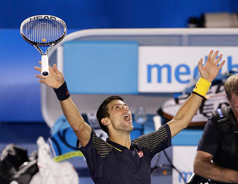 Novak Djokovic tosses his racquet as he celebrates his win over Andy Murray in the men's final at the Australian Open tennis championship in Melbourne, Australia, Sunday.