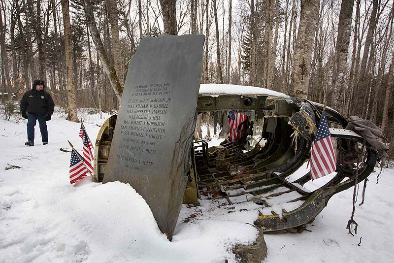 In this photo on Dec. 14, 2012, Greenville Police Chief Jeff Pomerleau views a monument next to wreckage from a B-52 bomber on Elephant Mountain near Greenville. The plane's 40-foot-tall vertical stabilizer had snapped off and crashed on Jan. 24, 1963. Seven of the nine people on board died in the crash.