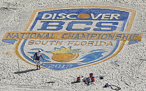 MAKING ART: An artist puts the finishing touches on the BCS National Championship logo on the beach Sunday in Fort Lauderdale, Fla. Notre Dame takes on Alabama for the national championship tonight in Miami.