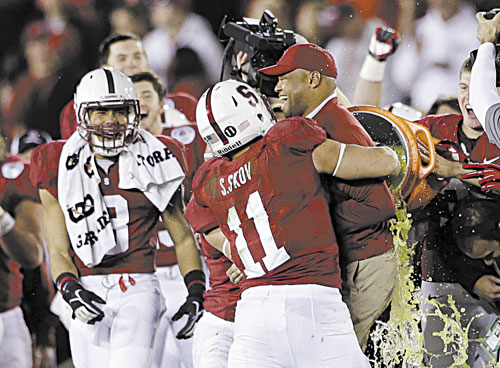 NICE WIN: Stanford head coach David Shaw is hugged by linebacker Shayne Skov (11) as he is doused following the Cardinal's 20-14 win over Wisconsin in the Rose Bowl on Tuesday in Pasadena, Calif.
