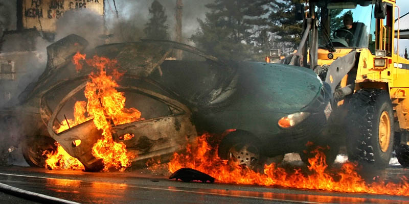 A 2000 Pontiac Grand Am burns on Norridgewock Road in Fairfield Tuesday. A nearby business owner, Bill Lybrook, tipped the car with a front-end loader to allow firefighters access to the undercarriage.
