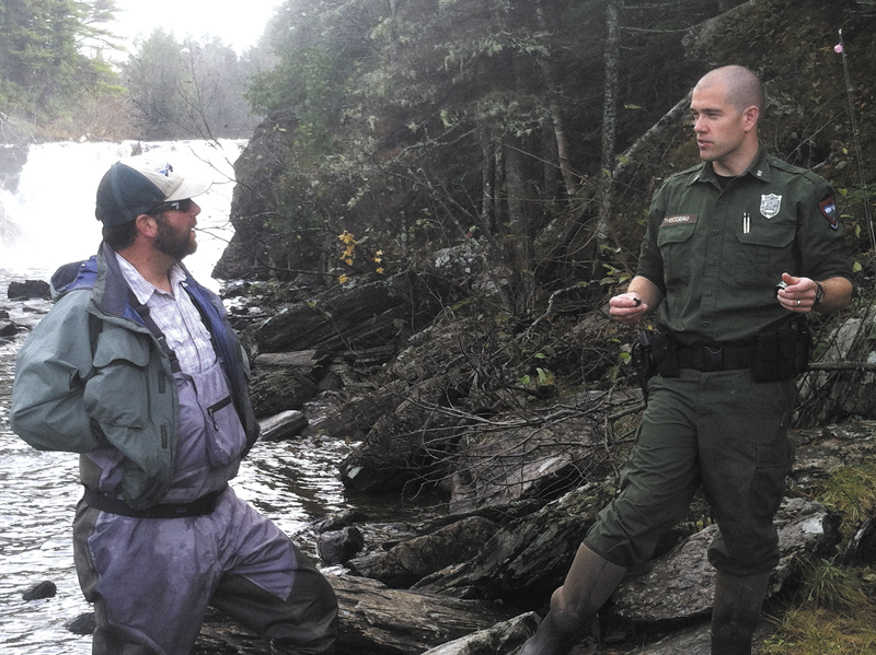 """District Game Warden Troy Thibodeau, of Augusta, confers with fly fisherman Ryan Cote, of Monmouth, beneath Grand Falls on the Dead River in an unorganized township in Somerset County. Thibodeau is featured in the television series """"North Woods Law."""""""