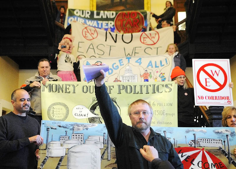 "Lew Kingsbury, of Pittston, holds up a megaphone after giving a speech on the steps in the Hall of Flags of the State House in Augusta on Tuesday. The Alliance for Common Good, featuring members of 20 interest groups, joined together for to hold a ""Rally of Unity"" on Tuesday January 8, 2013 in the State House's Hall of Flags in Augusta."