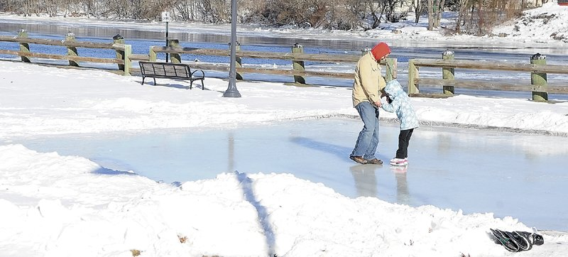 Manuel Manos, left, teaches Lily Matos to ice skate Saturday at the new rink beside the Kennebec River in Gardiner's Waterfront Park.
