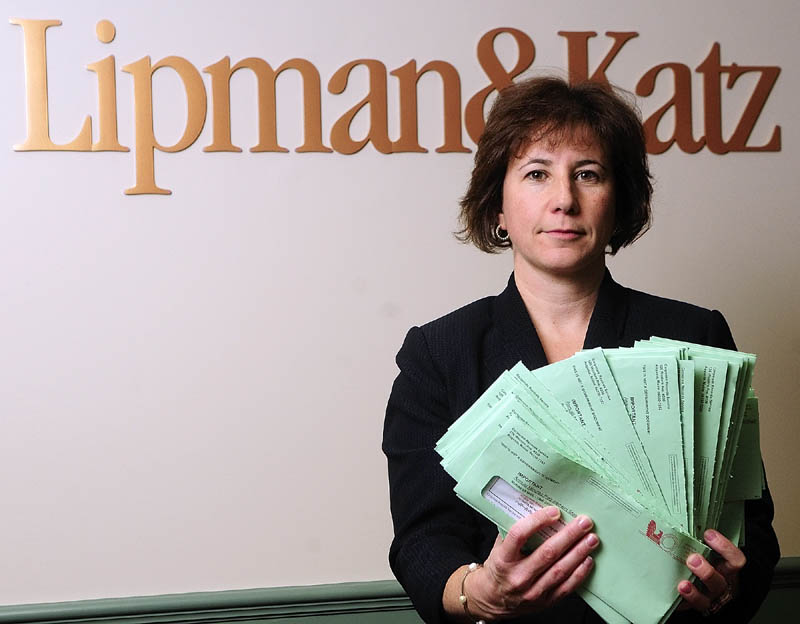 "Attorney Karen Boston displays about 60 letters received at the Lipman & Katz law firm on Wednesday in Augusta. The letters asked for corporate directors' names, addresses and $125 from ""Corporate Records Services."""