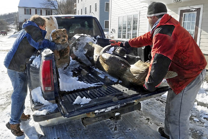 Don Bilodeau, left, moves a carved bear to make room for a life-sized sculpture of a person on Thursday. Bilodeau and artist Dan Burns were moving the sculpture from where it had been on display in Hallowell. Burns makes and sells chain saw sculptures outside McKenzie's Power Equipment on Route 17 in Augusta.