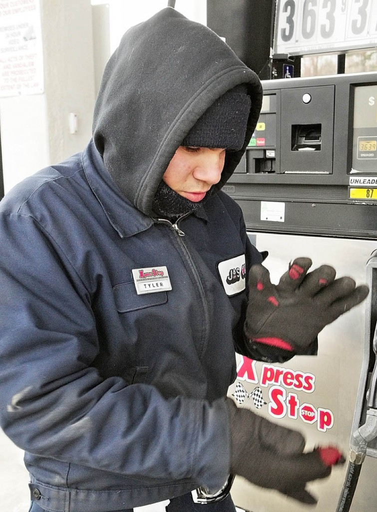 After putting his gloves on, Tyler Kalloch claps his hands to keep warm Tuesday while working the full service gas pumps at the J&S Oil Xpress Stop Convenience Store in Farmingdale. Kalloch said it helps to dress in several layers and to keep moving while working outside on cold mornings - such as the ones this week when the temperature dropped into the single digits.