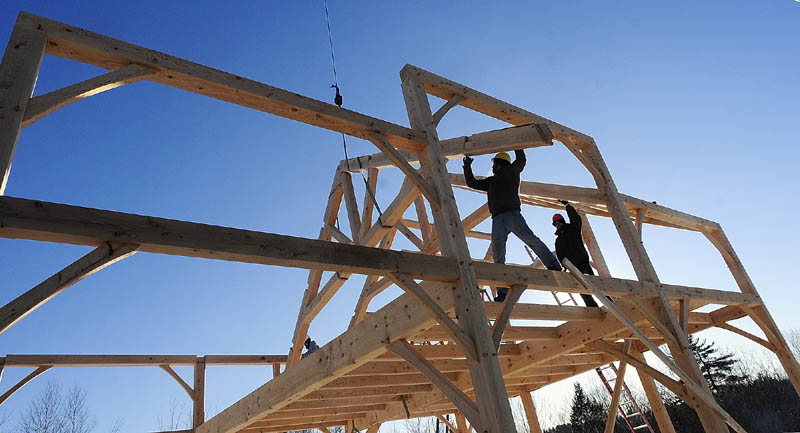 Workers lower a roof truss into position on Friday at the Grand View Timber Frames display site on Western Avenue in Manchester.