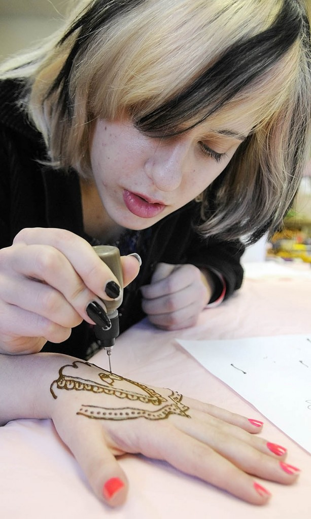 Meryl Kus draws a temporary tattoo on Cassidy Bane's hand on Saturday at the Gardiner Public Library.