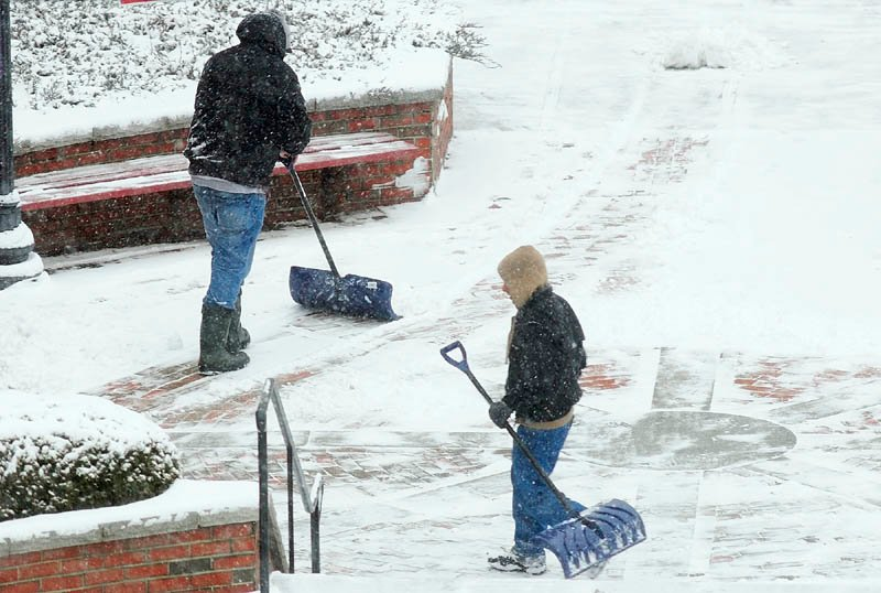 Workers shovels snow on Wednesday Jan. 16, 2013 in front of Key Plaza in downtown Augusta.