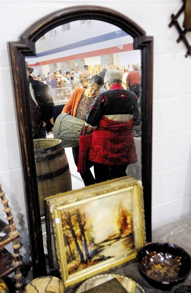 Meg Mourey, left, an antiques dealer from Lancaster, N.H., shows a piece of pottery to Miriam Buckley, of Damarine Antiques, on Tuesday at the 22nd annual New Year's Day Antique Sale at the Augusta armory. There were 45 antiques dealers at the show.