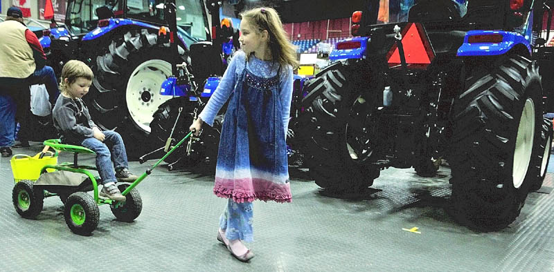 Oliver Kucharski, 3, left, gets a ride from his sister, Maya Kucharski, 8, both of Sidney, past some tractors at the Maine Agricultural Trades Show on Thursday at the Augusta Civic Center.